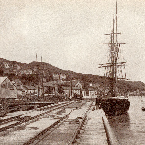 Black and white photo from 1800's of Aberdovey jetty with rail tracks and Cargo Clipper