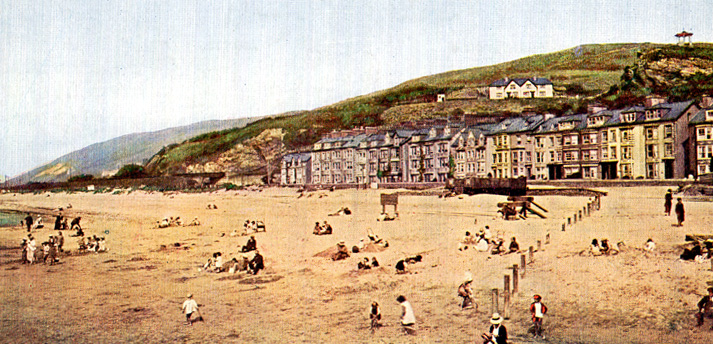 Early 1900's hand coloured photo of Aberdovey beach front, hillside and bandstand taken from the jetty